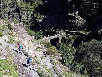 Foto von Wanderern in der Sierra Nevada mit alter Brücke übers Tal